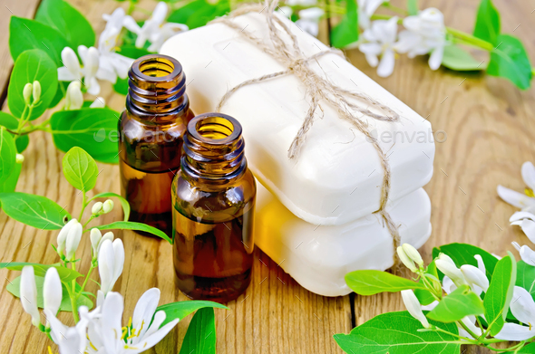 Oil and white soap with flowers of honeysuckle - Stock Photo - Images