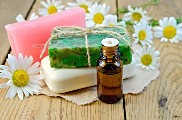 Oil with soap and camomile on board - Stock Photo - Images