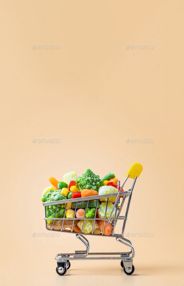 Frozen vegetables assorted on beige, vertical - Stock Photo - Images