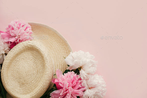 Straw hat with white and pink peonies on pastel pink paper, flat lay - Stock Photo - Images