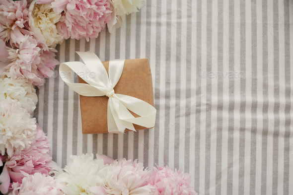 Craft gift box and peonies frame flat lay on rustic table cloth - Stock Photo - Images