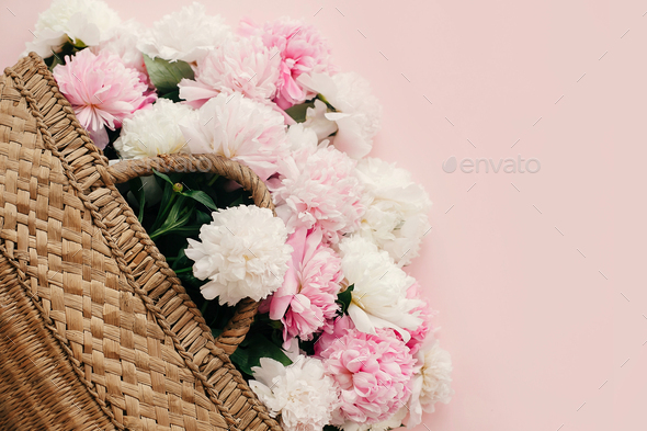 Stylish straw rustic bag with white and pink peonies on pastel pink paper - Stock Photo - Images