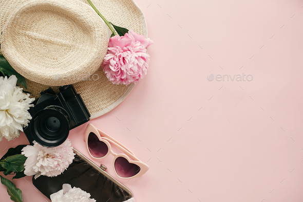 Stylish girly image of peonies, photo camera, retro sunglasses, hat, purse on pastel pink paper - Stock Photo - Images