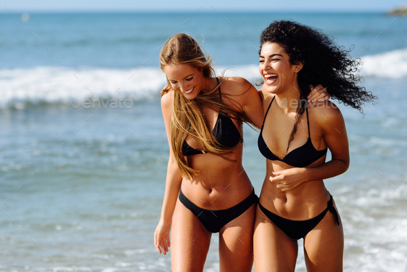 Two young women with beautiful bodies in swimwear on a tropical beach - Stock Photo - Images
