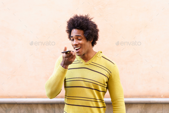 Black man with afro hair and headphones using smartphone - Stock Photo - Images