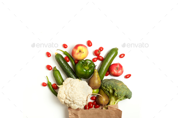 Paper bag of different healthy farm vegetables and fruits isolated on a white background - Stock Photo - Images