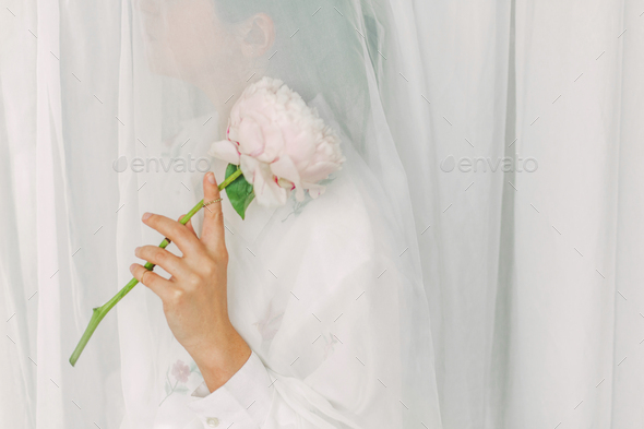 Aesthetic sensual image of beautiful woman holding pink peony flower through tulle - Stock Photo - Images