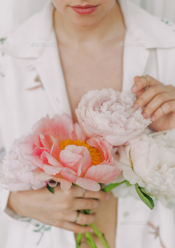 Stylish girl in white floral shirt gently holding peonies flowers in hands - Stock Photo - Images