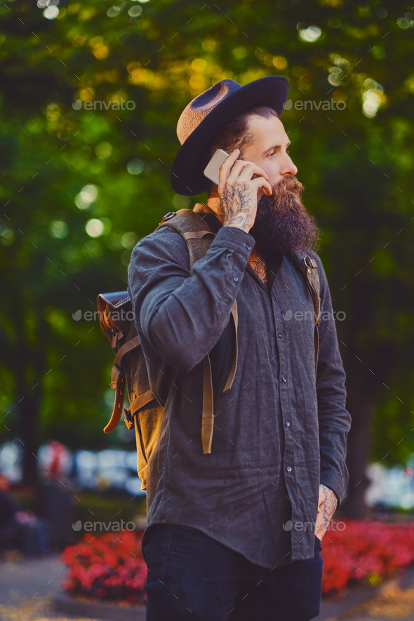 Bearded traveller male using a smartphone in a town. - Stock Photo - Images