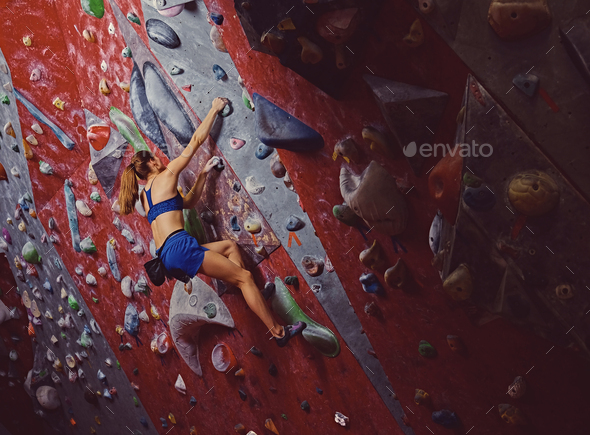 Professional female climber on a bouldering wall. - Stock Photo - Images