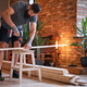 Carpenter drilling a hole in a board in a room with loft interior. - PhotoDune Item for Sale