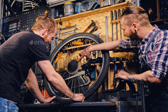 Bearded mechanics fixing bicycle's wheel in a workshop. - Stock Photo - Images