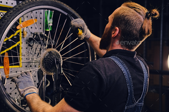 Mechanic repairing bicycle wheel tire in a workshop. - Stock Photo - Images