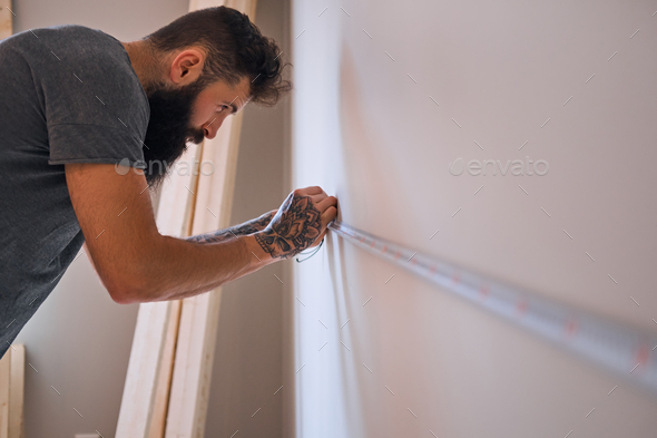 Carpenter measuring a wall. - Stock Photo - Images