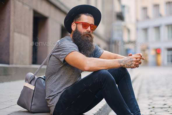 A man sits on a step on a street. - Stock Photo - Images