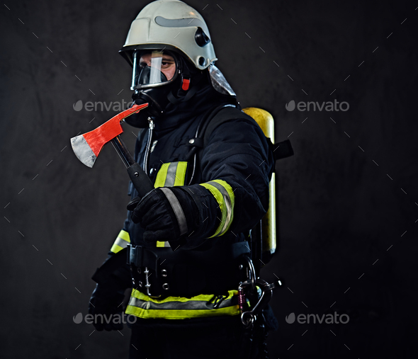 Firefighter dressed in a uniform holds a red axe. - Stock Photo - Images