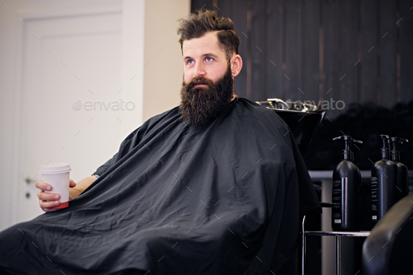 A man drinks coffee in a hairdresser's salon. - Stock Photo - Images