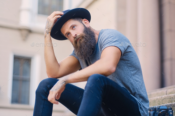 A man in a hat with tattoos on arms, sits on a step. - Stock Photo - Images