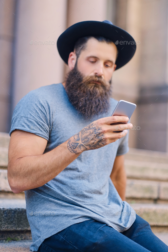 Bearded male in a hat holds a smartphone. - Stock Photo - Images