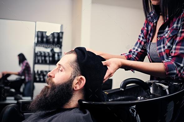 Hairdresser washing bearded men's hair. - Stock Photo - Images