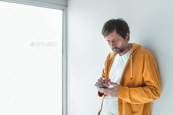 Man with yellow zip hoodie using mobile phone in morning - Stock Photo - Images