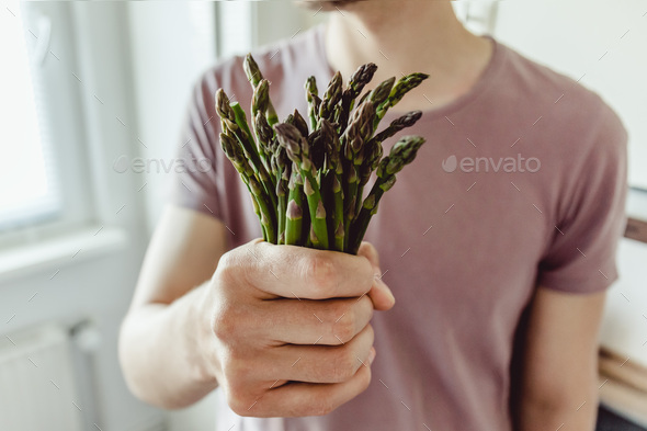 Young man holding fresh asparagus - Stock Photo - Images