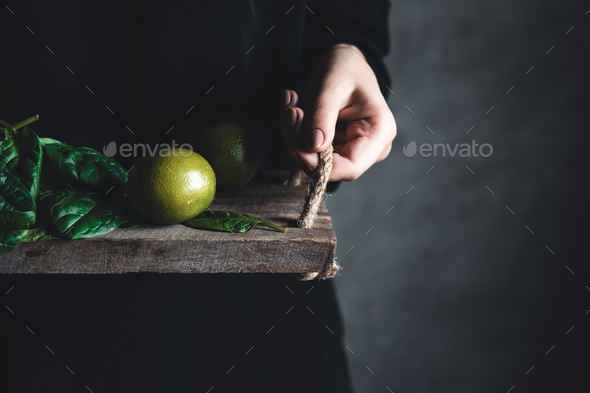 Girl holds on a vintage tray a spinach with lime. Vegan, wholesome food, eco - Stock Photo - Images