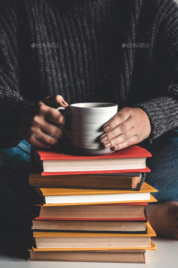 Stack of books with mug on top in front of woman reading book, education, training, hobbies - Stock Photo - Images