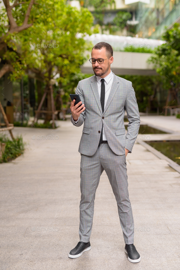 Full body shot of Hispanic bald bearded businessman using phone with eyeglasses in nature outdoors - Stock Photo - Images