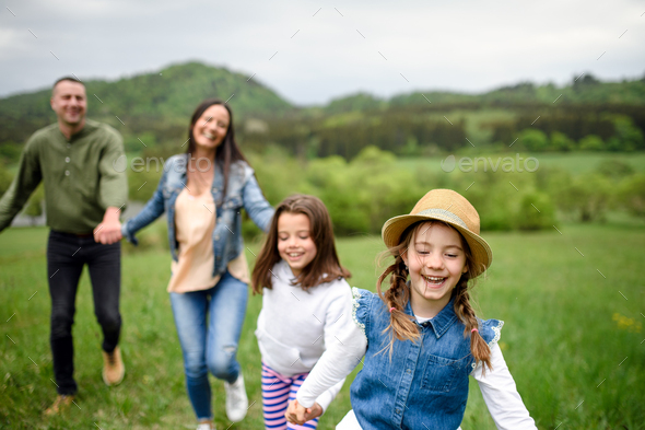 Happy family with two small daughters running outdoors in spring nature - Stock Photo - Images