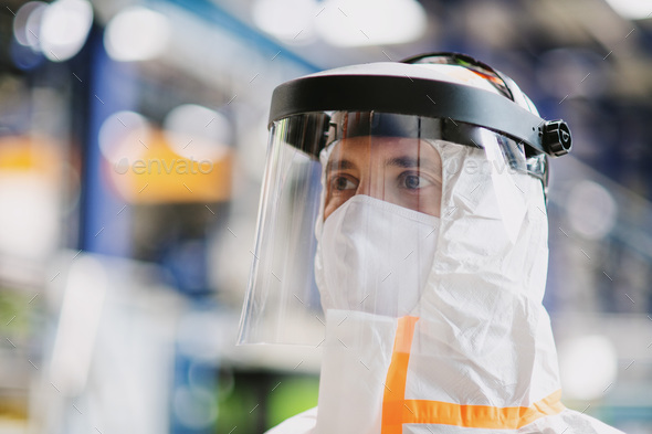 Close-up portrait of worker with protective mask and suit in industrial factory - Stock Photo - Images