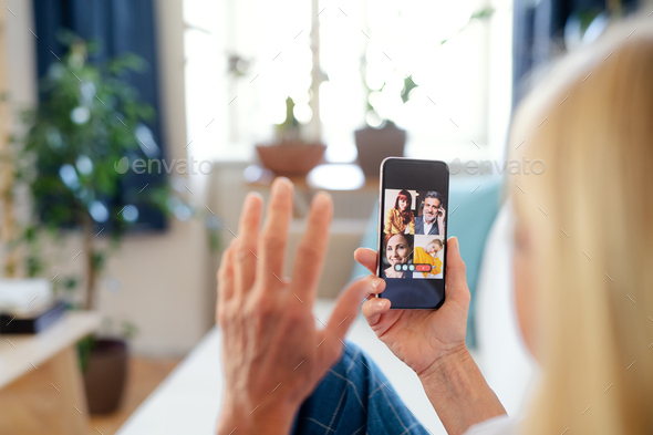 Senior businesswoman with smartphone indoors in home office, business call concept - Stock Photo - Images