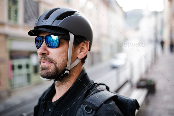 Delivery man courier with bicycle helmet and sunglasses in town - Stock Photo - Images