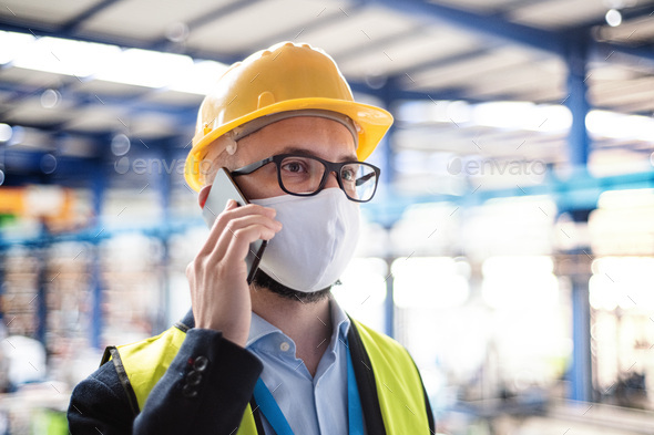 Technician or engineer with protective mask and telephone in industrial factory - Stock Photo - Images