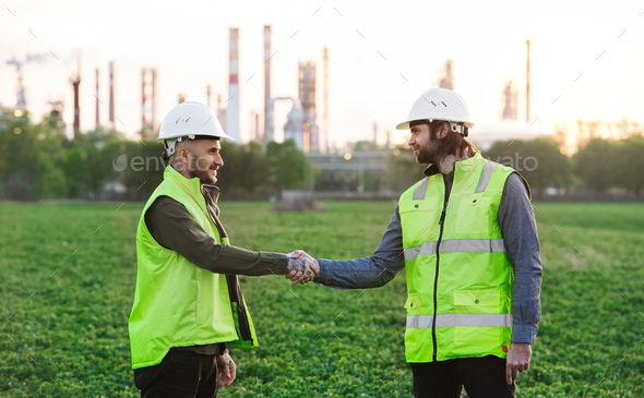 Two young engineers standing outdoors by oil refinery, shaking hands - Stock Photo - Images