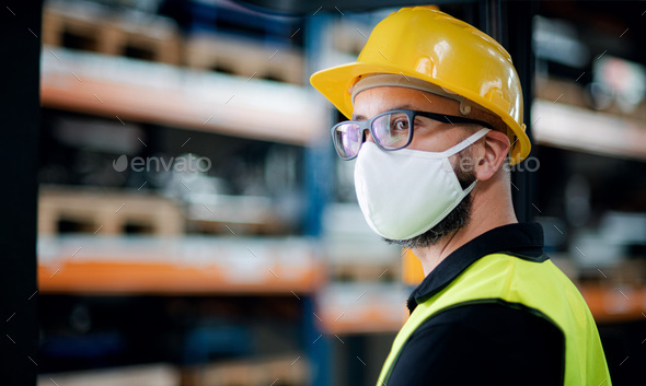 Technician or engineer with protective mask and helmet standing in industrial factory - Stock Photo - Images
