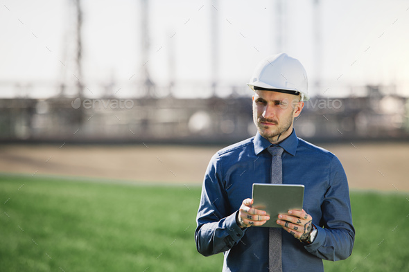 Young engineer with hard hat and tablet standing outdoors by oil refinery - Stock Photo - Images
