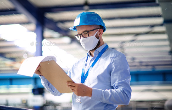 Technician or engineer with protective mask and helmet working in industrial factory - Stock Photo - Images