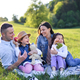 Happy family with two small daughters sitting outdoors in spring nature, having picnic - PhotoDune Item for Sale