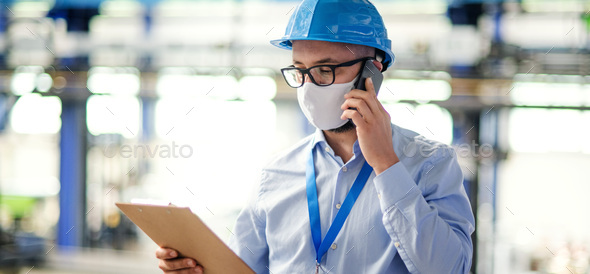 Technician or engineer with protective mask and telephone working in industrial factory - Stock Photo - Images