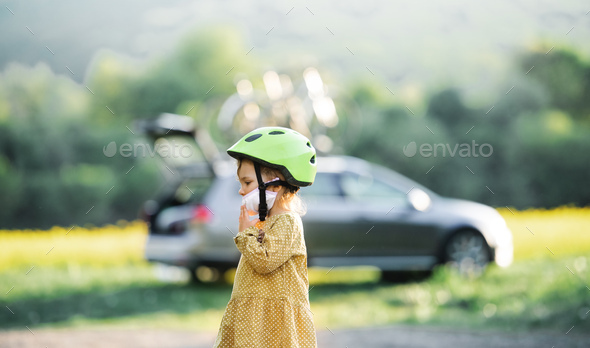 Side view of small girl with bicycle helmet on cycling trip in countryside - Stock Photo - Images