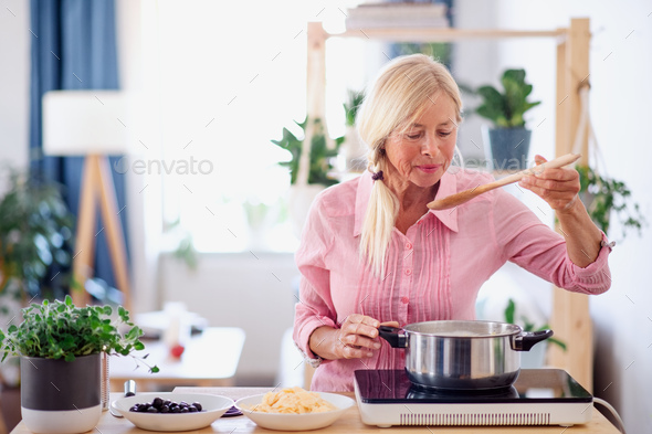 Senior woman cooking in kitchen indoors, stirring pasta in pot - Stock Photo - Images