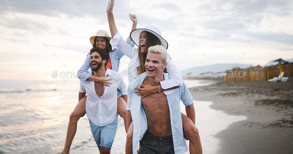 Group happy friends enjoying beach, summer vacation together - Stock Photo - Images