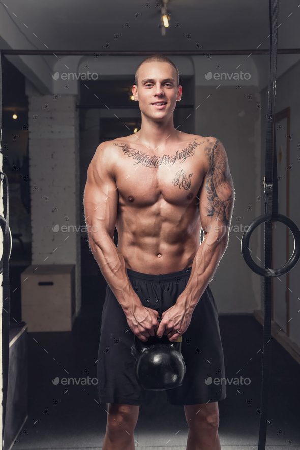 Tattooed shirtless man holds lifting weight. - Stock Photo - Images