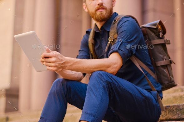A man sits on a step and using a tablet PC. - Stock Photo - Images