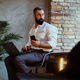 Urban bearded male using a laptop in a room with loft interior. - PhotoDune Item for Sale