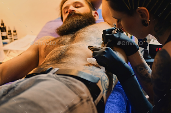 Female tattoo artist makes tattoo on bearded male torso in a salon. - Stock Photo - Images