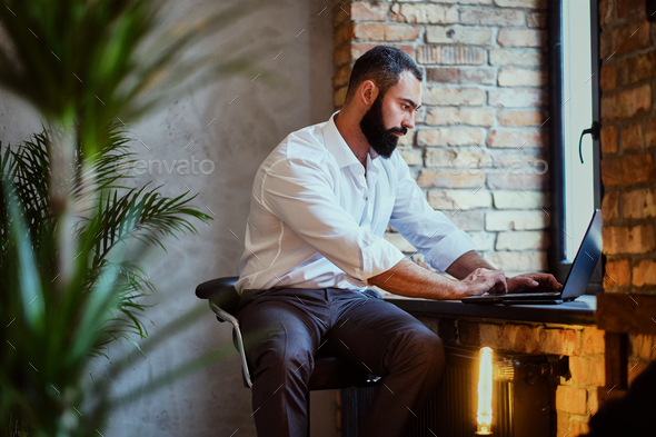 Stylish bearded male works with a laptop. - Stock Photo - Images