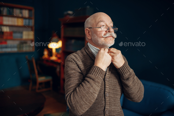 Elderly man puts on a tie in home office - Stock Photo - Images