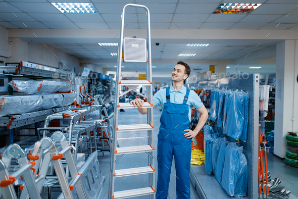 Worker holds aluminum stepladders in tool store - Stock Photo - Images